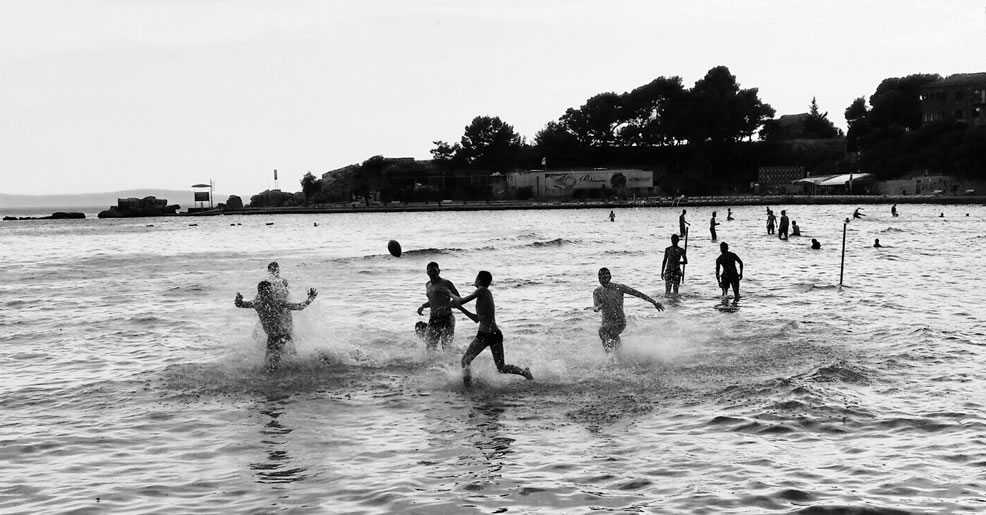 Children playing rugby in the sea at twilight.