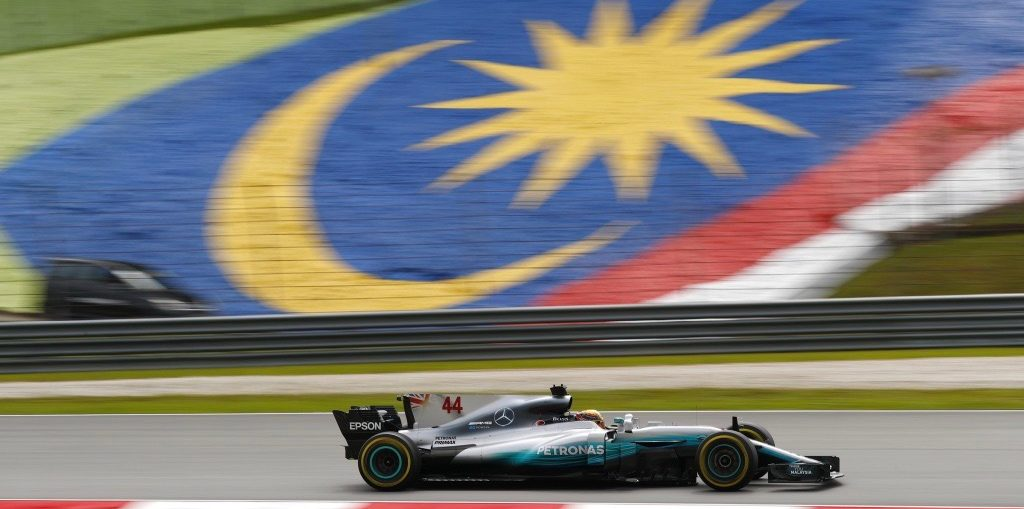 Mercedes Formula One car driving past Malaysian flag