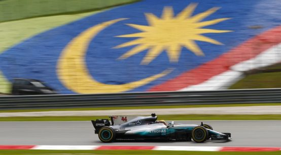 Mercedes Formula One car driving past Malaysian flag