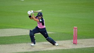 Middlesex left-handed batter Max Holden plays a drive. He is wearing Middlesex's one-day kit: pink shirt with blue sleeves, blue trousers, pads and helmet, with white batting shoes and batting gloves.