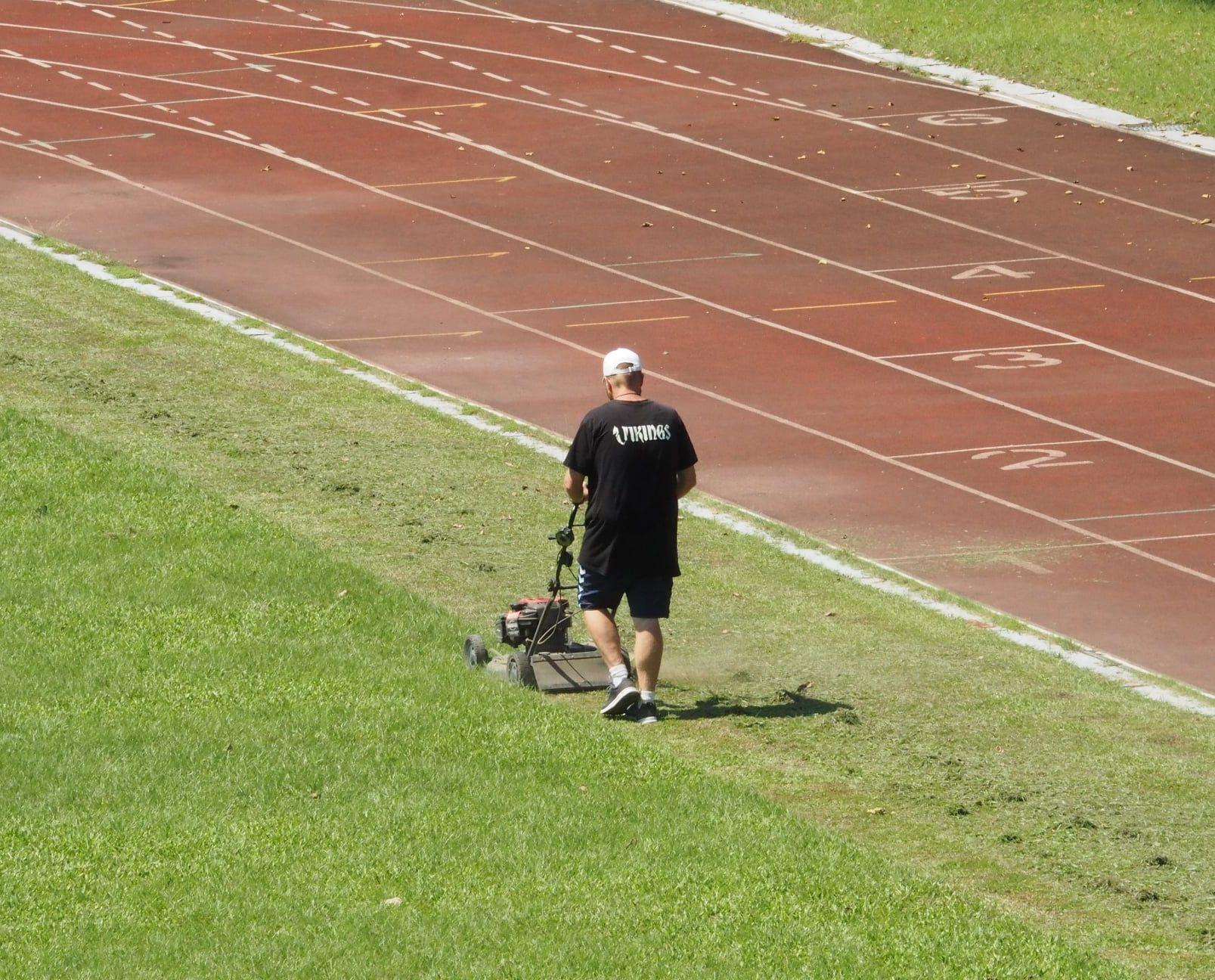 Football coach Johnni Nielsen mowing the pitch.