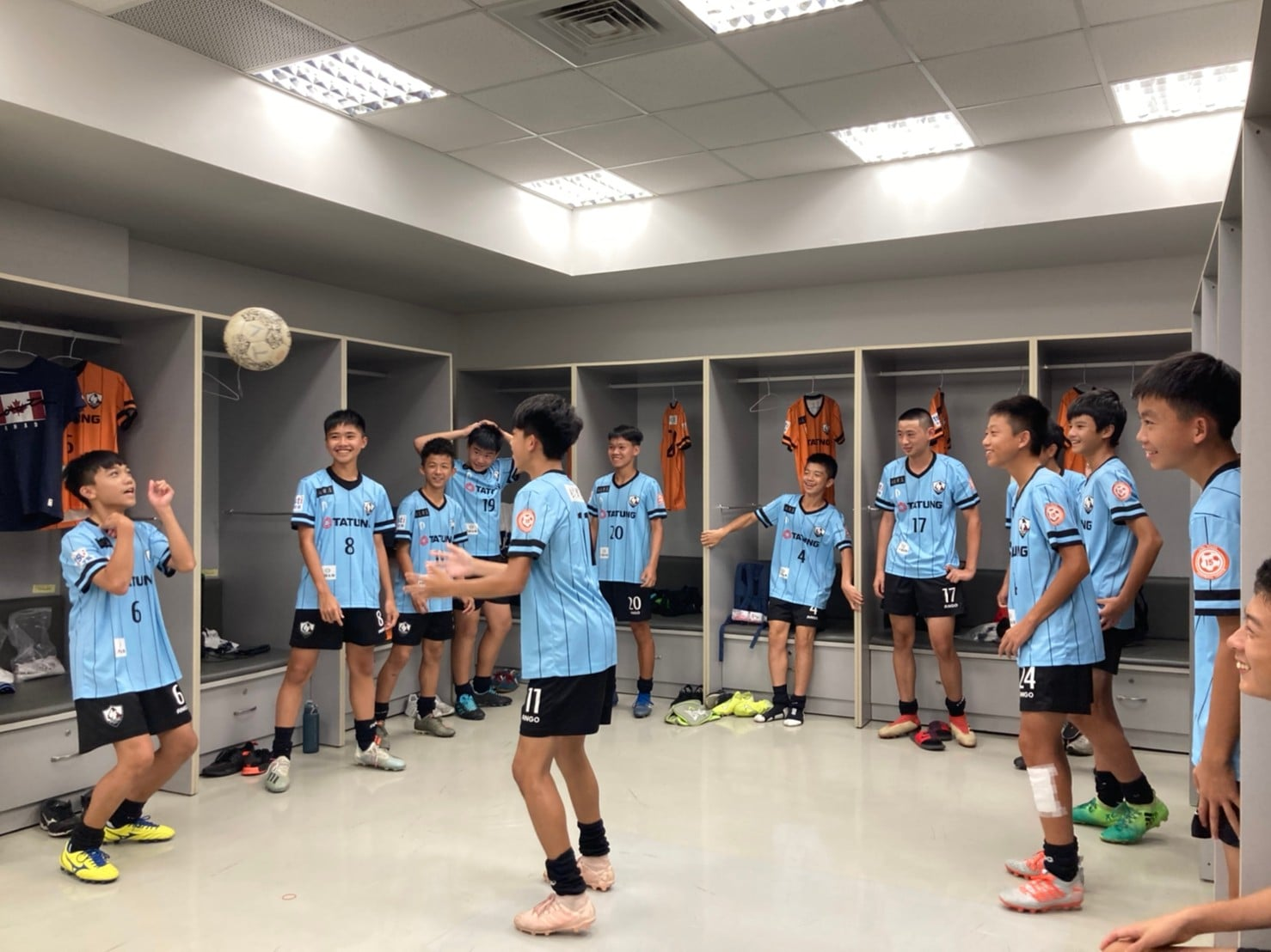 An age-group team for FC Vikings warm up in the dressing room just before kick-off with a game of head tennis.