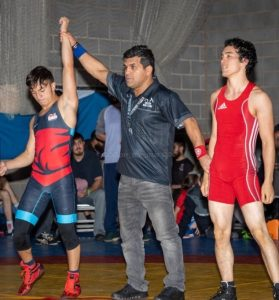 Yahia with hand raised winning the gold medal at the Derbyshire Invitational