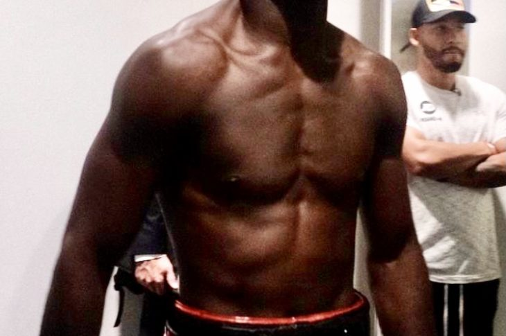 Boxer Joshua Buatsi readies himself in his dressing room. He is topless, and is wearing black shorts with a red waistband and black boxing gloves.