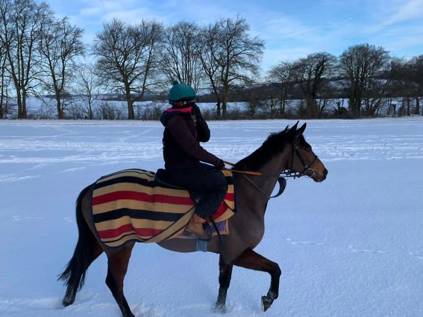 Jockey Georgie Dobie, dressed in black with a green helmet, goes for a training gallops at a snow-covered yard. The horse is wearing a red, white and blue striped blanket.