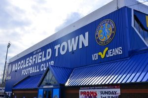 The outside of Macclesfield Town FC's stadium, Moss Rose, a blue corrugated iron building with the club's name, crest and lead sponsor in large letters.