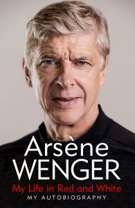 The cover of Arsène Wenger's autobiography, titled 'My Life in Red and White', featuring a head and shoulders photo of Wenger, a tall thin man with medium length grey hair dressed in a dark shirt.