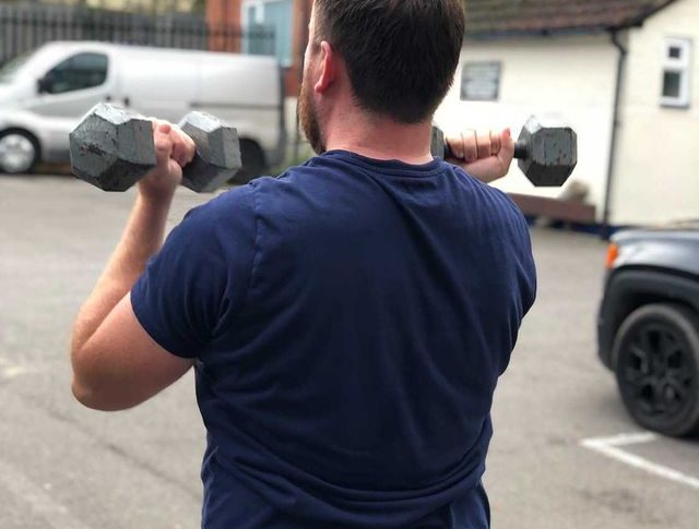 A personal trainer, wearing a blue t-shirt and blue gym shorts, trains clients in a car park during England's second lockdown of November 2020.