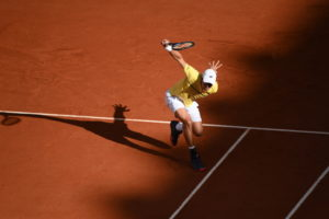Tennis player Daniel Altmaeir, wearing a yellow shirt, white shorts, cap and socks, and black shoes, plays a single-hand backhand at Roland Garros