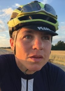 Endurance cyclist Emily Chappell, wearing black colours with a white stripe down the centre and a green and black helmet, finds time for an in-race selfie