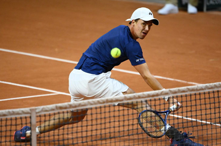 Tennis player Daniel Altmaier, wearing a blue shirt, white shorts, socks and cap and black shoes, plays a low backhand volley at Roland Garros