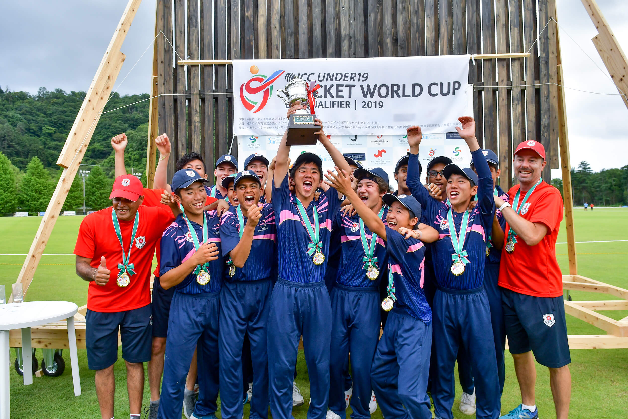 Japan's U19 men's cricket team, in a blue kit with pink details, celebrate qualification for the U19 World Cup