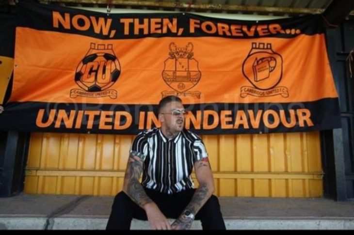 Former Cambridge United footballer Liam Hughes, sitting in front of a Cambridge United flag looking pensive