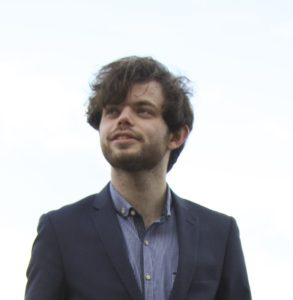 Robbie Owen, creator of Squidge Rugby. He is white, with medium length brown hair and designer stubble, and is wearing a navy blue blazer and blue button-down shirt.